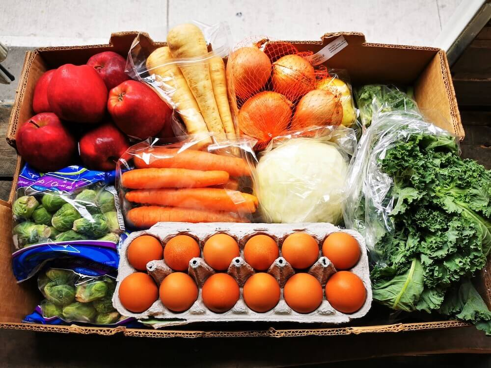 a box of fresh produce including eggs, carrots, apples and vegetables
