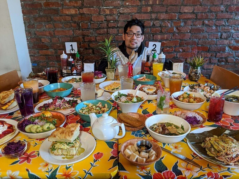 Chick-fil-A Team Member Yunha Moh sits behind a table full of dishes that were on the menu at his former Brooklyn restaurant, Tamra Teahouse.