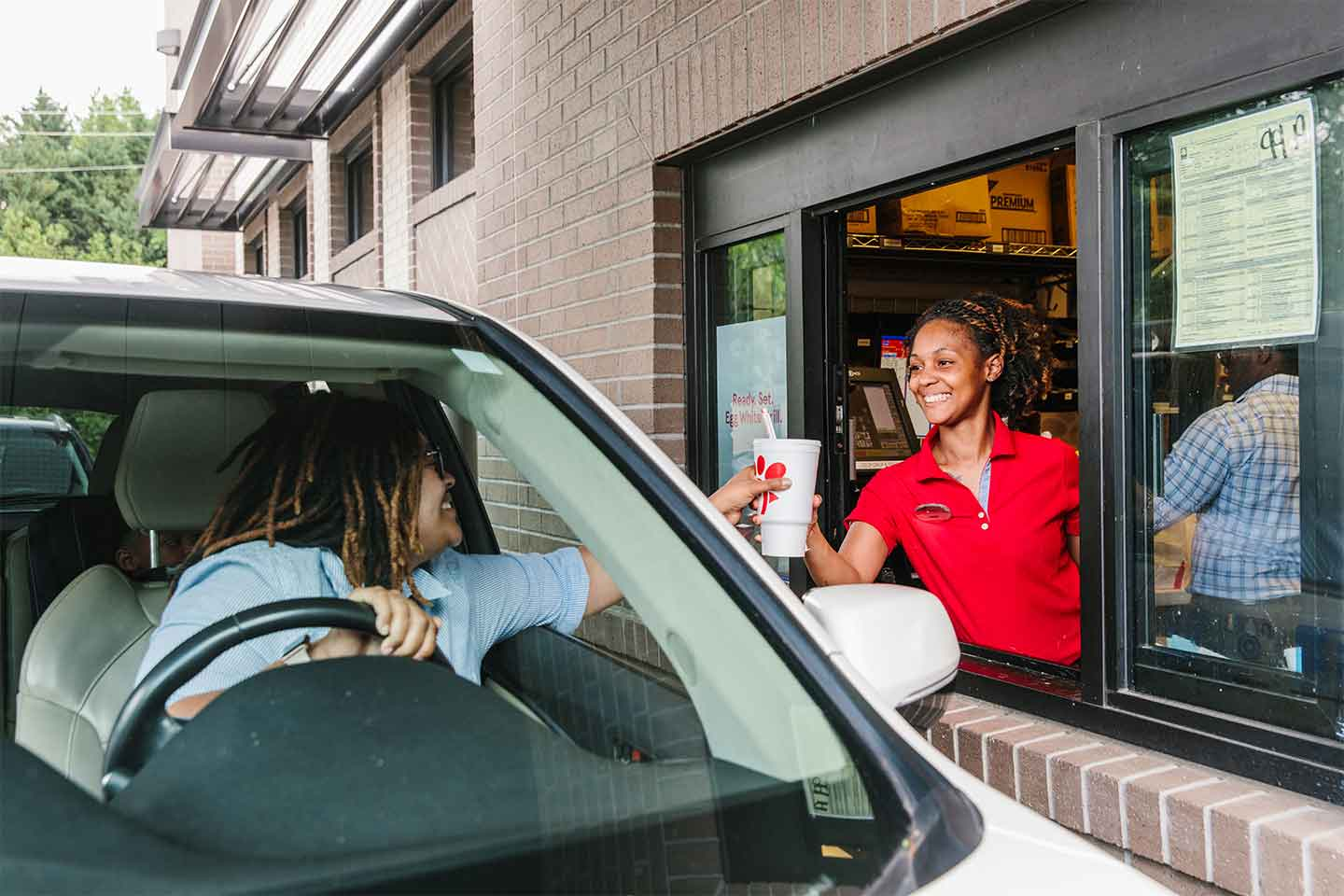 Chick-fil-A representative and customer interaction in the drive thru.