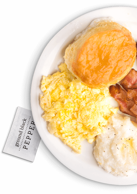 Partial image of a plate of grits, scrambled eggs, bacon and a biscuit