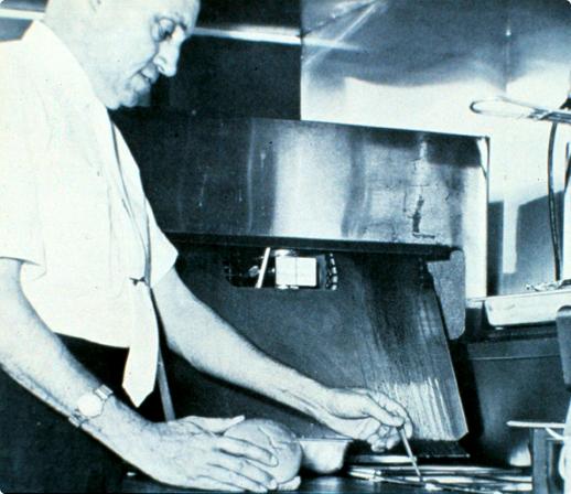 Truett Cathy making chicken sandwich on the grill