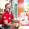 Team member wearing a cow-spots mask looks at the camera as she passes the customer their food tray while wearing gloves
