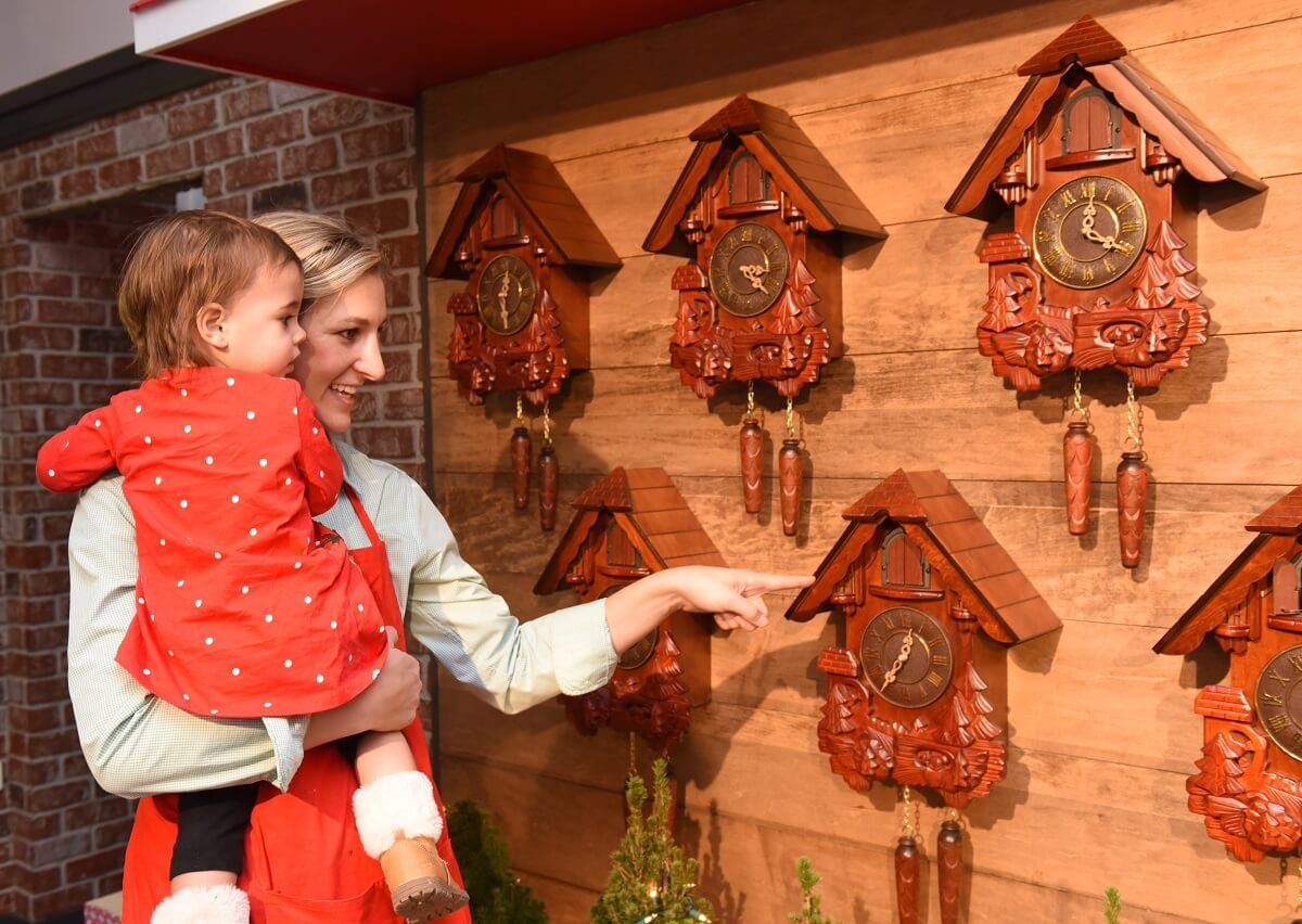 a woman holding a toddler looking at a wall of clocks