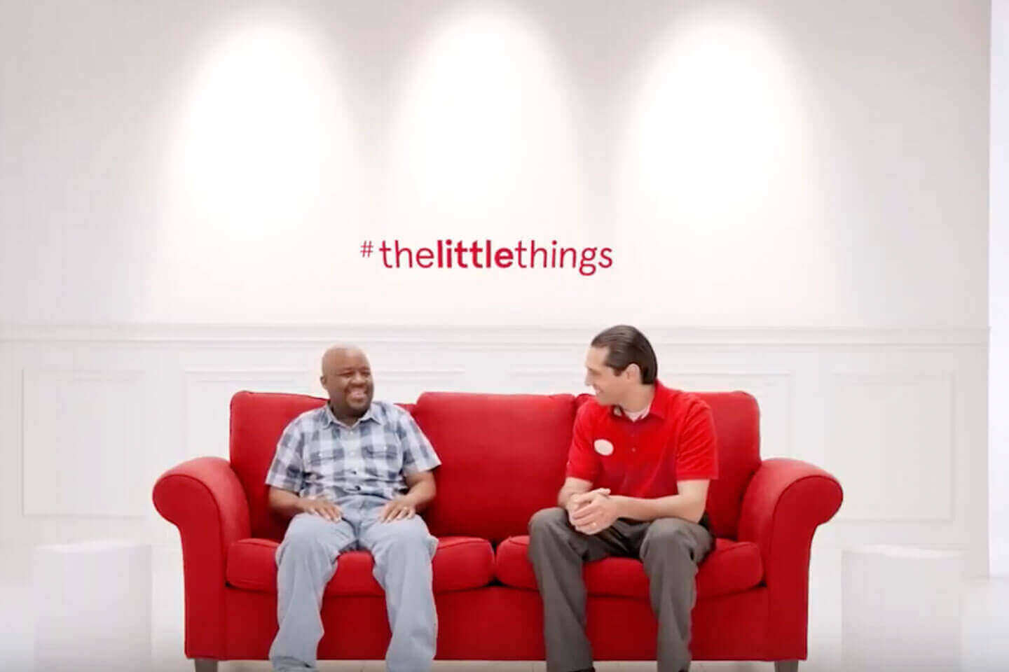 Chick-fil-A employee and customer sitting on red couch