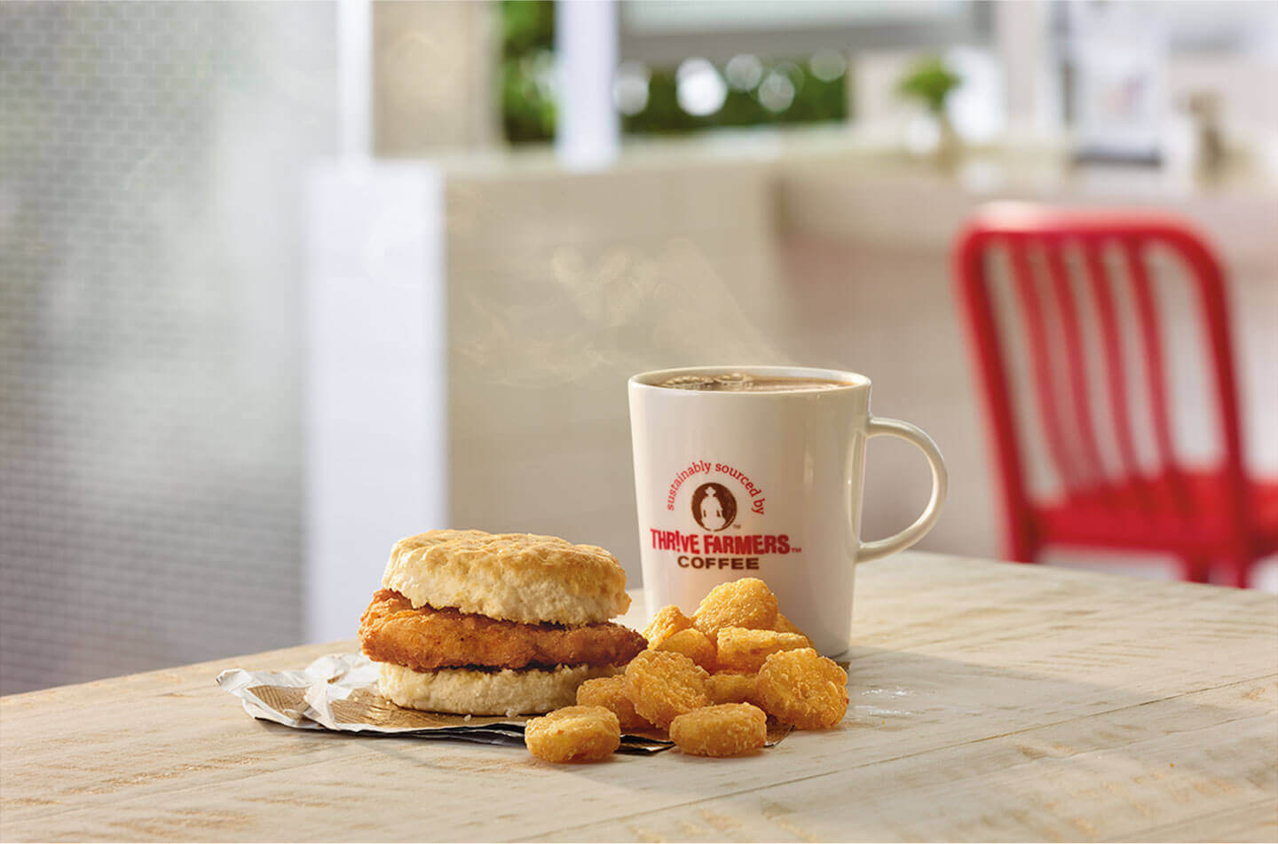 A cup of coffee, chicken biscuit and hashbrowns