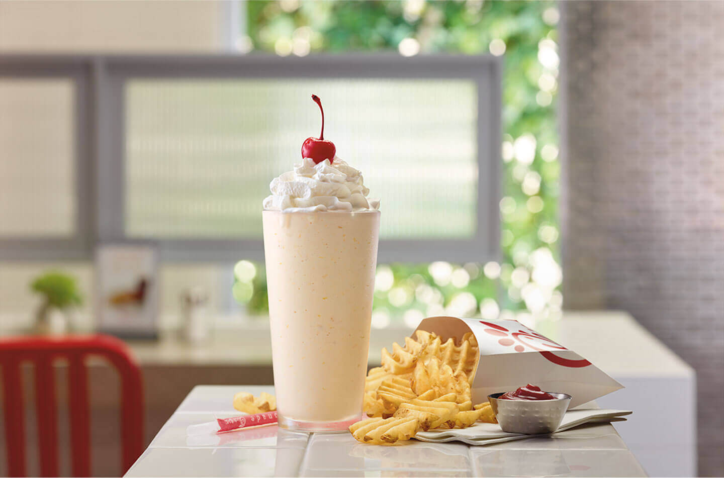 Peach milkshake with whipped cream and a cherry and a side of french fries