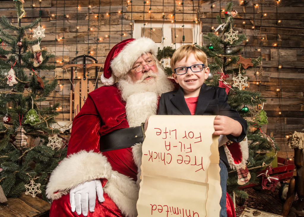 "Little boy sitting on santa's lap with his christmas list reading ""free Chick-fil-A for life"""
