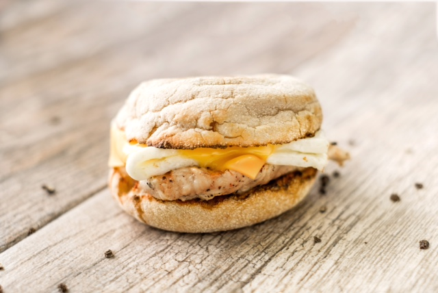 Egg white grill with egg whites, American cheese, and grilled chicken on a toasted English Muffin