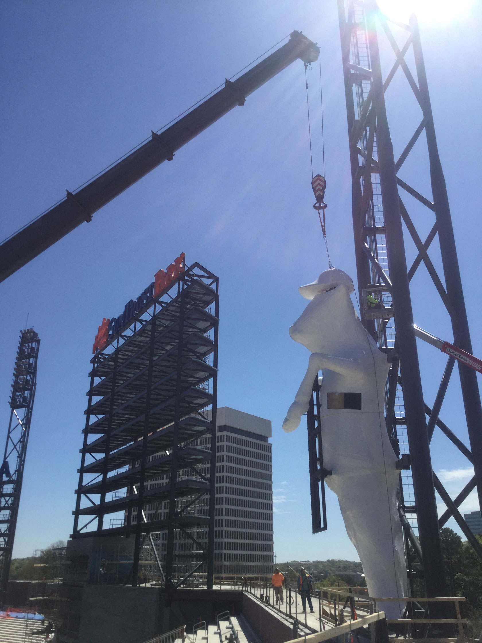 The 40-foot icon is hoisted into SunTrust Park in a protective wrap that shields it from debris
