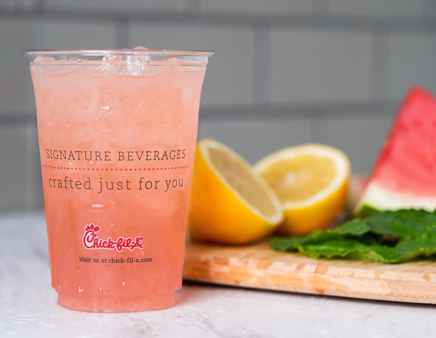 Chick-fil-A watermelon mint lemonade with sliced lemon, mint, and watermelon in the background.