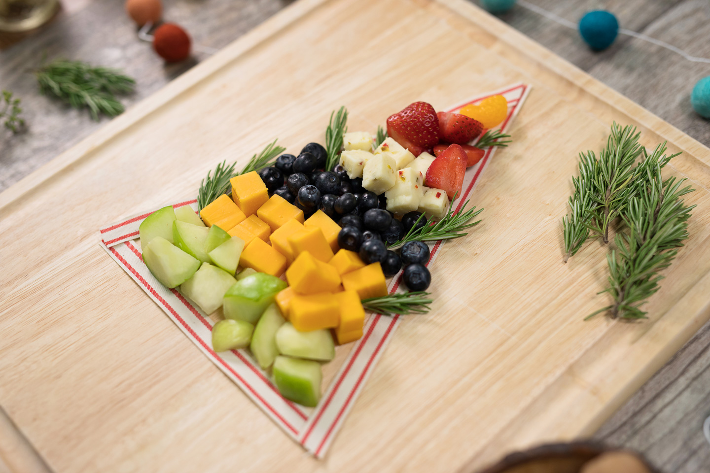 Christmas tree outlined on a board filled with cheese and fruit from a Chick-fil-A Fruit Tray garnished with rosemary.