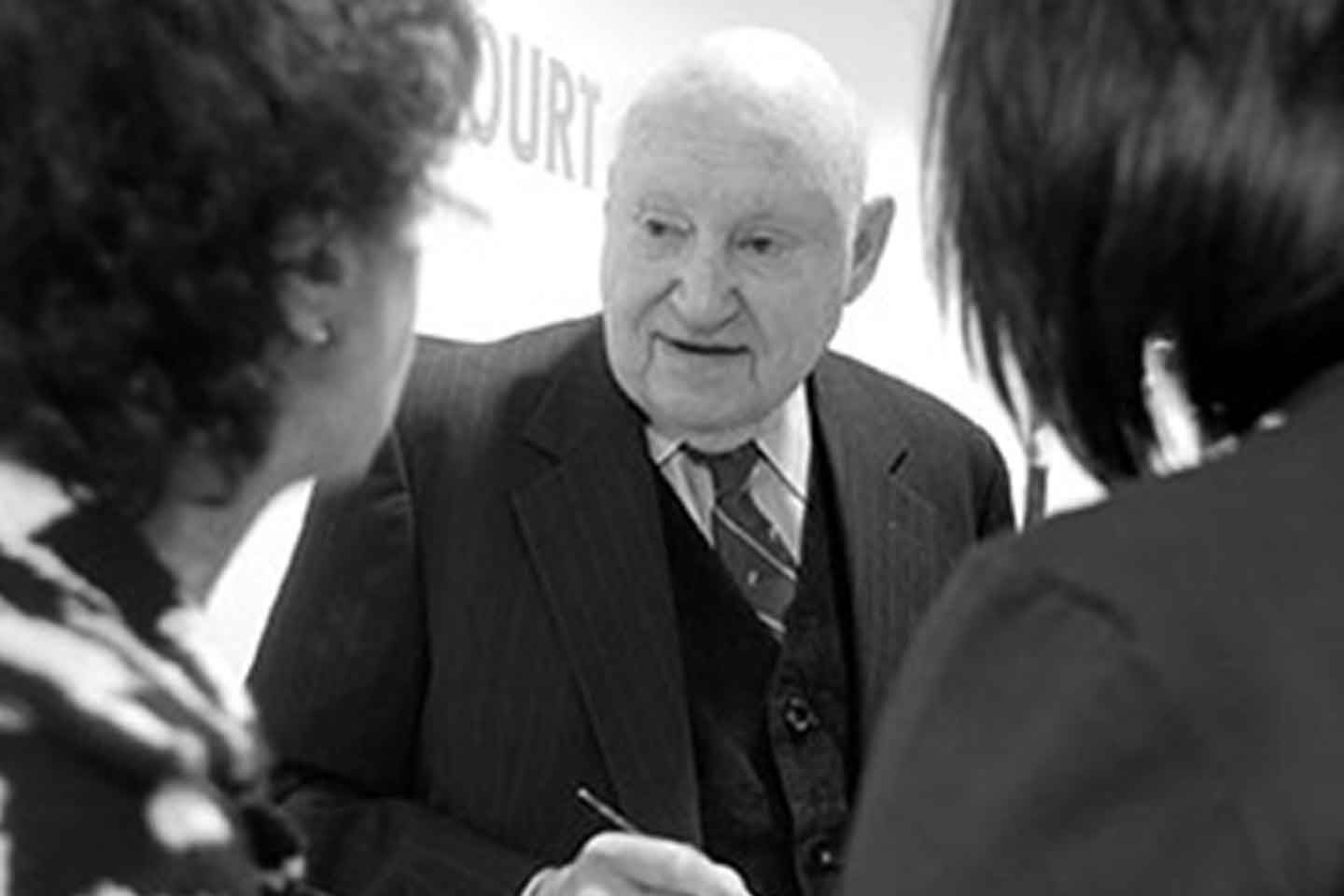 Truett Cathy speaks with two women