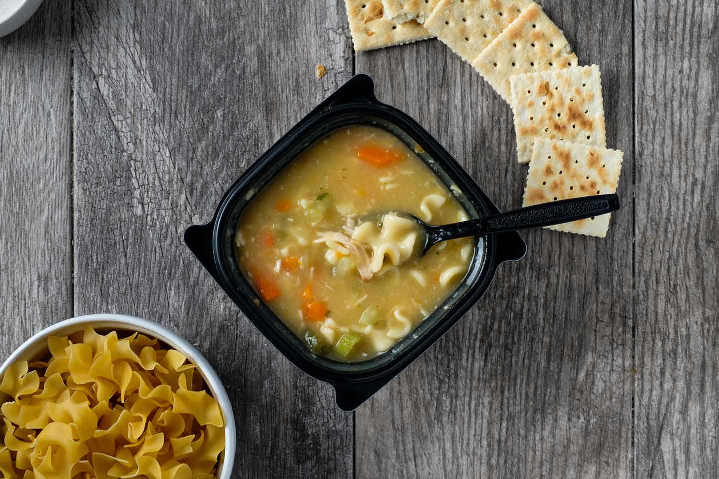 Chick-fil-A Chicken Noodle Soup in a black container on a wooden table.
