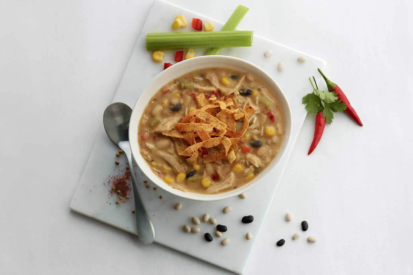 Bowl of Chick-fil-A Chicken Tortilla Soup surrounded by beans, corn, celery and a spoon.