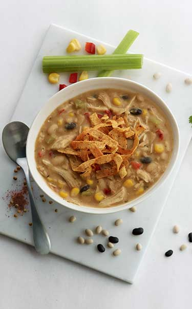 Chick-fil-A Chicken Tortilla Soup in a bowl surrounded by beans, peppers and celery.