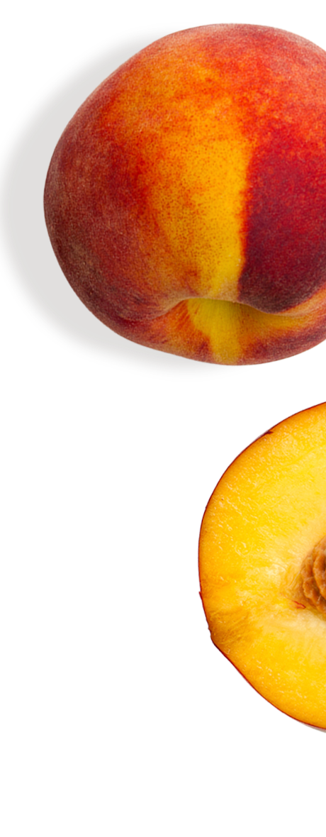 Two peaches; one halved and one whole